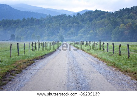 Unpaved country road and pasture lined  with rail fence - stock photo