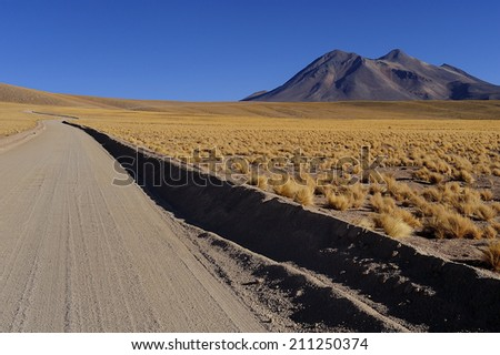 Unpaved dirt road at Altiplano high plateau, Atacama Desert, Chile - stock photo