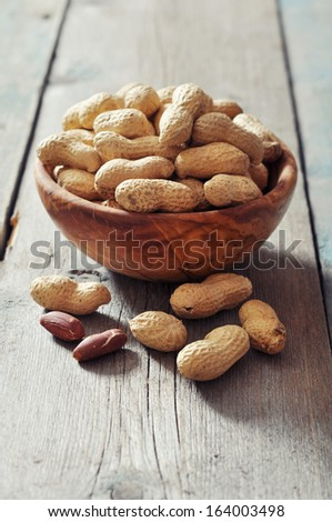 Unpeeled  peanuts in bowl on wooden background closeup