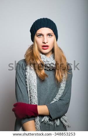 unpleasantly surprised blonde girl, dressed in winter clothing, Christmas and New Year concept, studio photo isolated on a gray background