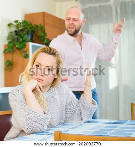 Unpleased man and young woman during quarrel in living room at home - stock photo