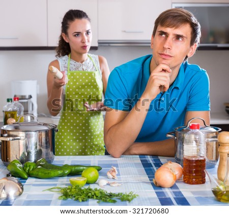 Unpleased woman criticizing young spouse in domestic kitchen - stock photo