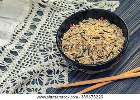 Unpolished brown and black rice in wooden bowl, chopsticks on wooden background with rustic doily crochet. Healthy food - stock photo