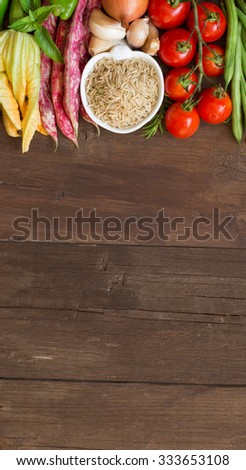 Unpolished raw rice and vegetables on a wooden background