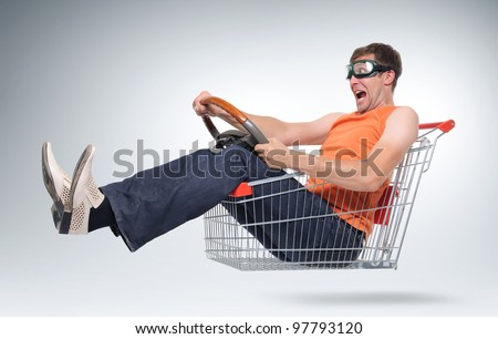 Unreal crazy driver in a shopping-cart with wheel, concept car shopping - stock photo