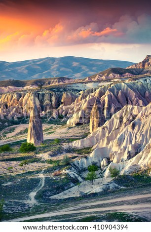 Unreal world of Cappadocia. Sunrise in Red Rose valley in April. Chavushin  village located, district of Avanos in Nevsehir Province in the Cappadocia region of Turkey, Asia. - stock photo