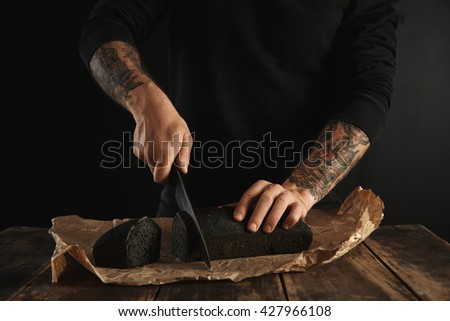 Unrecognizable baker in black sweatshot with tattooed hands cut freshly baked homemade charcoal bread with big chief knife on slices on craft paper on wooden rustic table ready for sale