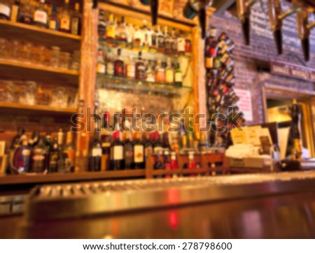 Unrecognizable bar counter and bottles background blurred filter - stock photo