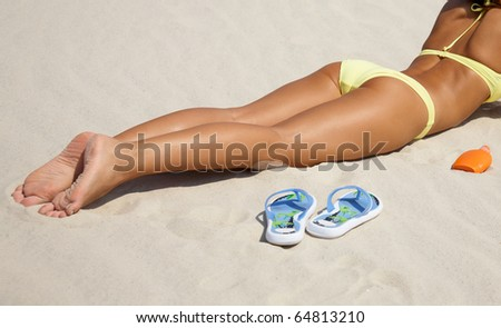 Unrecognizable beautiful young woman in bikini lying and sunning on the beach under the bright sun - stock photo