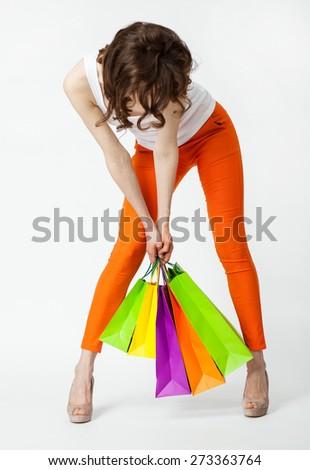 Unrecognizable brunette in orange pants holding shopping bags, full length portrait on neutral background - stock photo