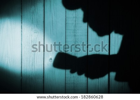 Unrecognizable burglar with  flashlight  in shadow on wood background, with space for text or image - stock photo