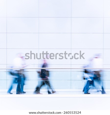 Unrecognizable business people in a fair hall, intentional motion blur, blue tinted photo  - stock photo