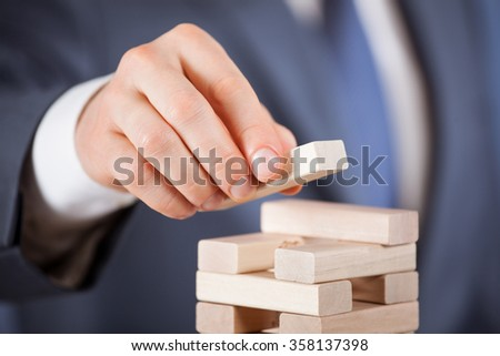Unrecognizable businessman forming a wooden pyramid - closeup shot - stock photo