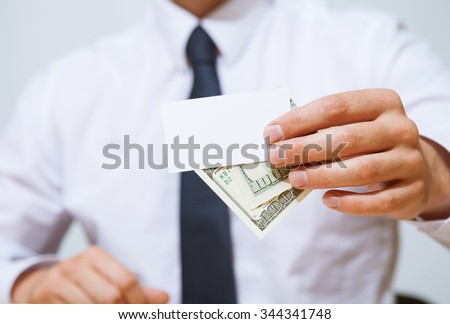 Unrecognizable businessman giving a hundred dollars and business card, closeup shot - stock photo