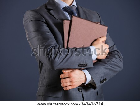 Unrecognizable businessman holding folders with documents. dark background