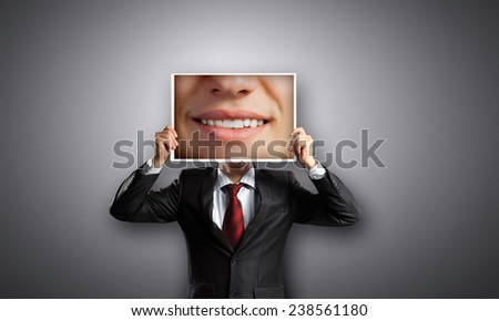 Unrecognizable businessman holding photo with smiling mouth - stock photo