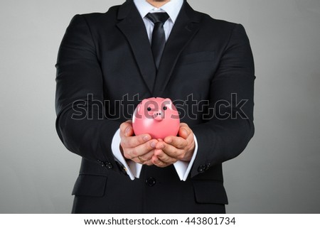 Unrecognizable businessman holding pink piggy bank