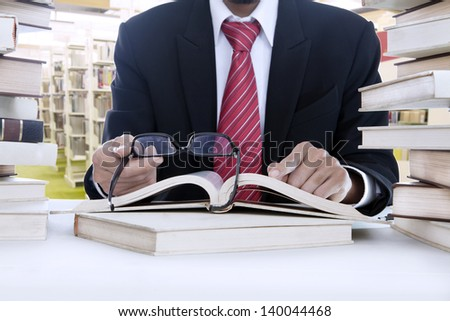 Unrecognizable businessman is reading with glasses in the library - stock photo