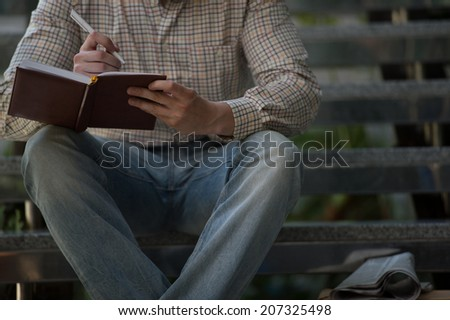 Unrecognizable businessman making notes sitting on stairs inside office building - stock photo