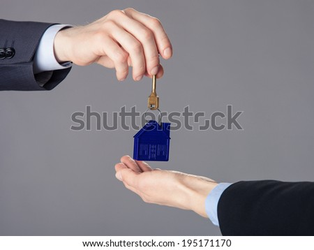 Unrecognizable businessman passing a key to woman's hand, closeup shot - stock photo