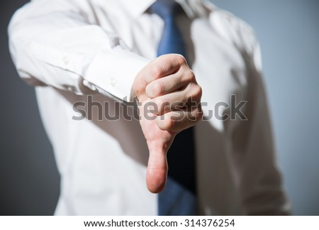 Unrecognizable businessman showing thumb down, dark background