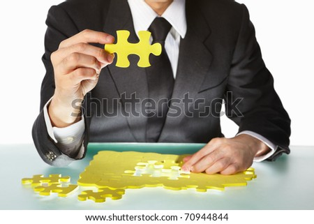 Unrecognizable Businessman trying to finish the puzzle