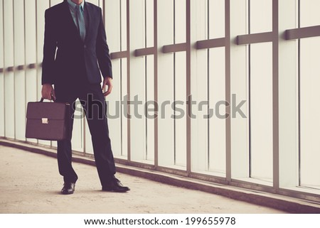 Unrecognizable businessman with a briefcase standing in the office building - stock photo
