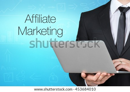 Unrecognizable businessman with laptop standing near text - affiliate marketing - stock photo