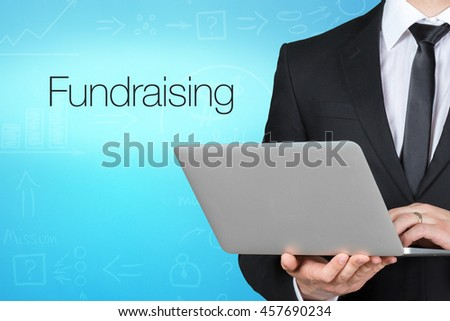 Unrecognizable businessman with laptop standing near text - fundraising - stock photo