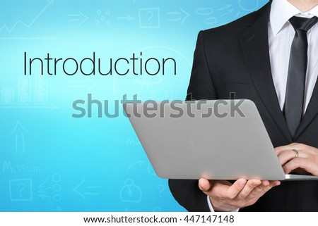 Unrecognizable businessman with laptop standing near text - introducion - stock photo