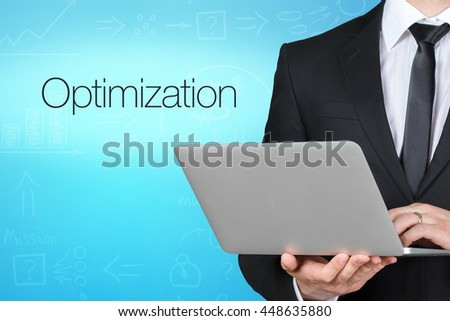 Unrecognizable businessman with laptop standing near text - optimization - stock photo