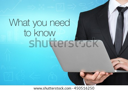 Unrecognizable businessman with laptop standing near text - what you need to know - stock photo