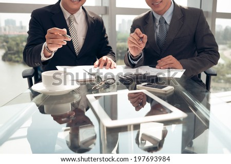 Unrecognizable businessmen pointing at the digital tablet with their pens: modern business concept - stock photo