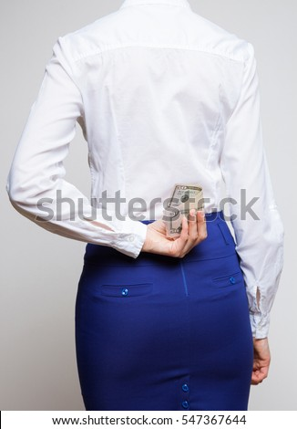 Unrecognizable businesswoman hiding dollars behind back