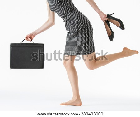 Unrecognizable businesswoman running and holding her shoes and a briefcase, white background - stock photo