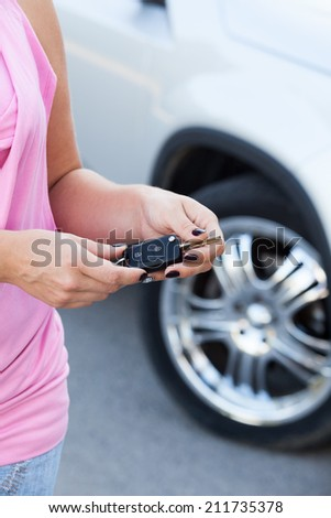 Unrecognizable Caucasian woman with ignition key standing near new car - stock photo