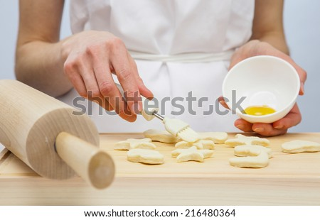 Unrecognizable cook spreading uncooked pastry with yolk - stock photo