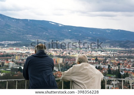 Unrecognizable couple of old seniors looks around from lookout tower on city and hills in the background. Melancholic atmosphere of contemplation and peace of retirement