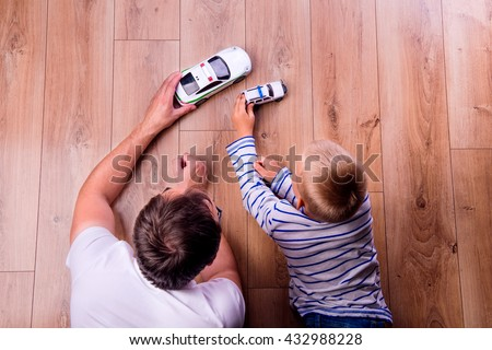 Unrecognizable father with his son playing with cars - stock photo