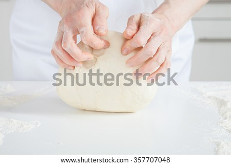 Unrecognizable female cook kneading dough on the table - stock photo