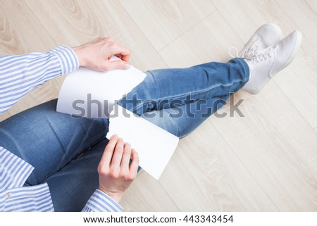 Unrecognizable female hands tearing blank paper - upper viewpoint