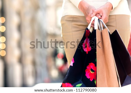 Unrecognizable female shopper holding three shopping bags - stock photo