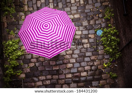 Unrecognizable female under umbrella walking on paved street - stock photo