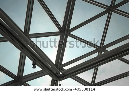 Unrecognizable fragment of modular / structural glass ceiling against sky. Glazed aluminum structure with triangular pattern. Abstract architectural background composition. - stock photo