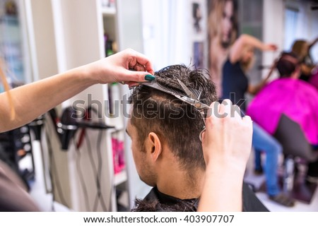 Unrecognizable hairdresser cutting hair of her young client.