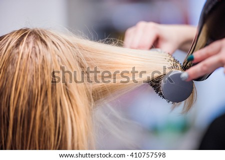 Unrecognizable hairdresser drying hair of her beautiful young cl - stock photo