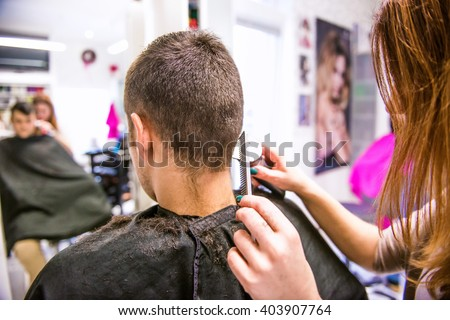 Unrecognizable hairdresser shaving head of her young client.