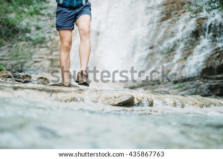 Unrecognizable hiker young woman walking along the river on background of waterfall in summer outdoor, view of legs