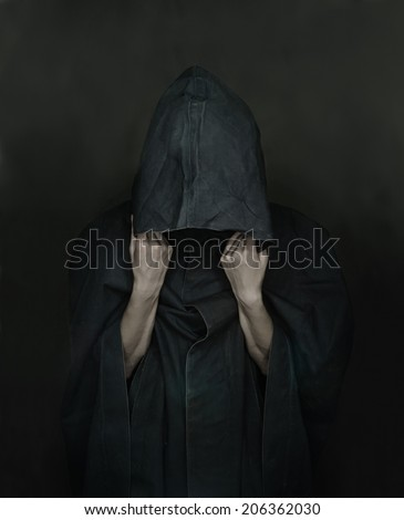 Unrecognizable human in black coat with a hood, face is not visible - stock photo