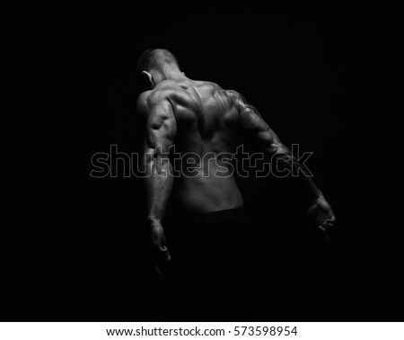 Unrecognizable man bodybuilder shows strong back muscles, athletic trapezius. Black and white, studio shot on black background.